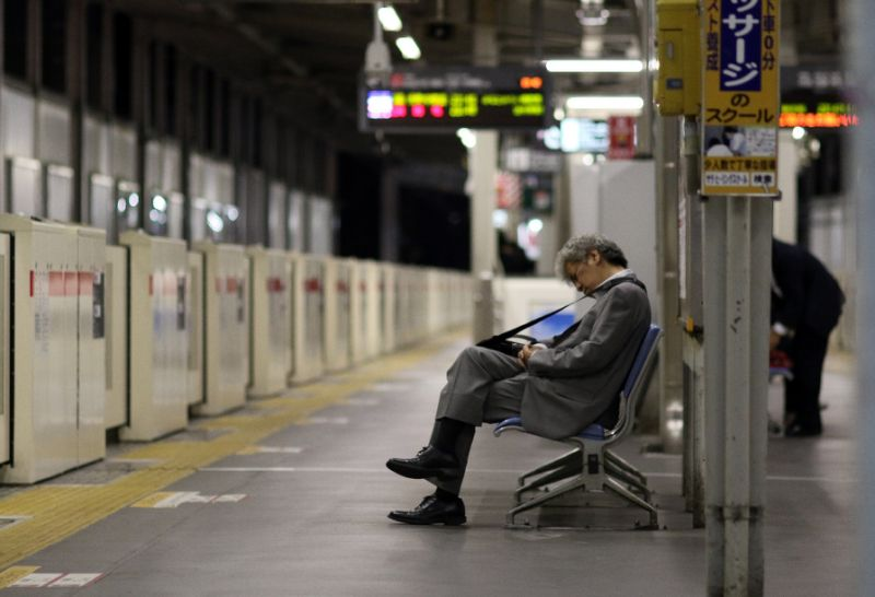 a businessman is seen napping on a bench at a tokyo train station photo afp
