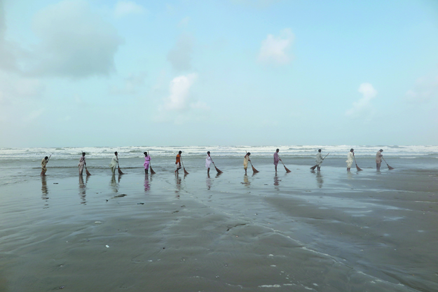 Hard at work: The artists hired 11 cleaners from Cantonment Board Clifton for a day and asked them to sweep all the sand from the beach into the ocean that the DHA forces them to do. PHOTO: KOEL GALLERY