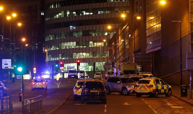 Vehicles are seen near a police cordon outside the Manchester Arena, where U.S. singer Ariana Grande had been performing, in Manchester, northern England, Britain, May 23, 2017. PHOTO: REUTERS