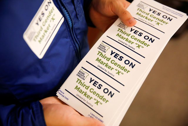 an employee of the advocacy group basic rights oregon hands out stickers during an oregon driver and motor vehicle department public hearing on the rights of transgender people as the state considers adding a third gender choice to driver 039 s licenses and identification cards in portland oregon may 10 2017 photo reuters