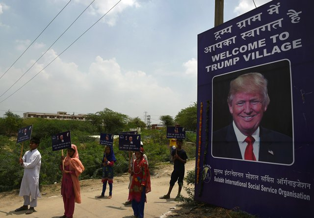 "Indian children hold placards by the entrance gate of Marora village, which has been unofficially renamed 'Trump Village,"" about 100km from New Delhi, on June 23, 2017.  PHOTO: AFP"