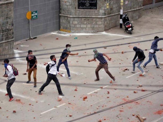 Demonstrators throw stones towards the Indian police during a protest in Srinagar. PHOTO: REUTERS