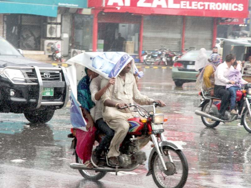 bikers take shelter from the rain under a panaflex photo abid nawaz express