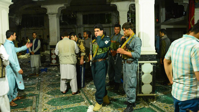 Afghan security personnel inspect the site after the suicide bomb attack at a Shia mosque in Herat. PHOTO: AFP