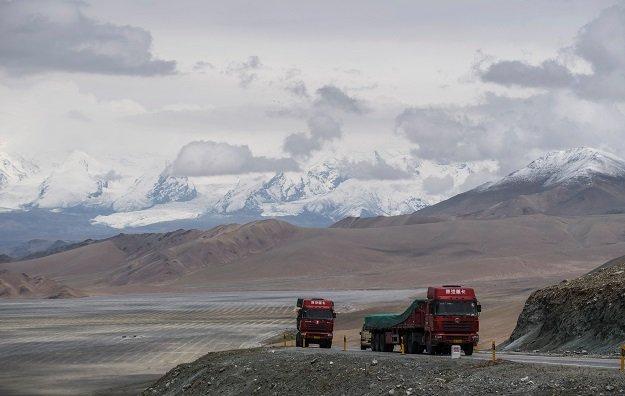 trucks driving along the china pakistan friendship highway before the karakorum mountain range near tashkurgan in china 039 s western xinjiang province photo afp