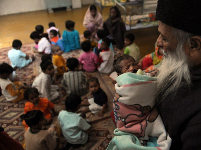 in this photograph taken on december 6 2010 abdul sattar edhi head of pakistani 039 s edhi foundation holds a disabled orphan at the orphanage of the charity in karachi photo afp