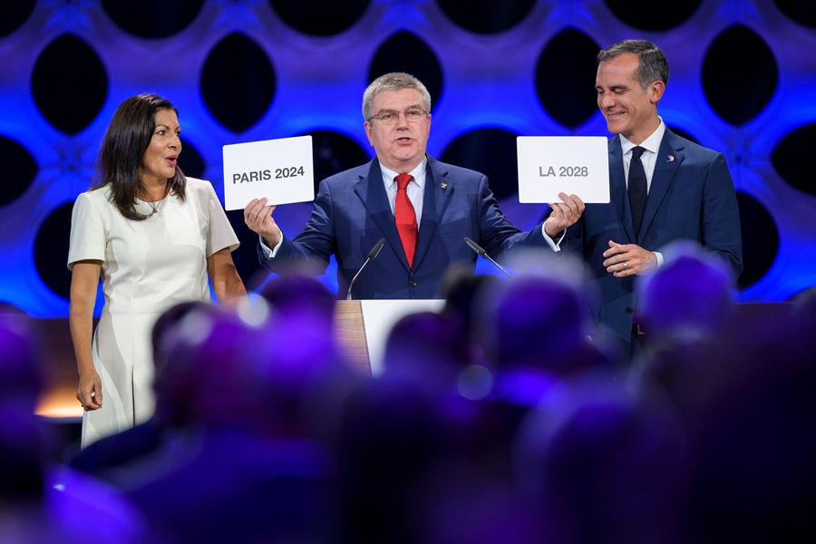 International Olympic Committee (IOC) President Thomas Bach (C) holds the cards bearing the name of Paris 2024 and Los Angeles 2028 next to both cities' mayors Anne Hidalgo (L) and Eric Garcetti during the 131st IOC session in Lima on September 13, 2017. PHOTO: AFP