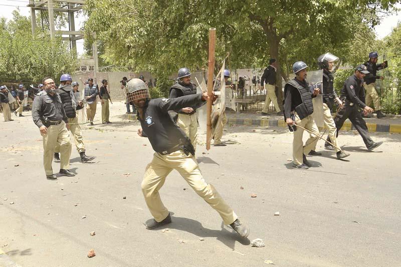 A file photo of policemen responding to Qadri supporters in Model Town. PHOTO: SHAFIQ MALIK