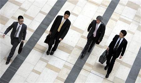 Businessmen walk on a street. PHOTO: REUTERS