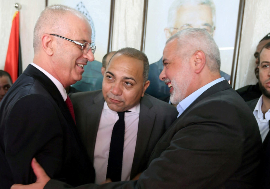 Prime Minister Rami Hamdallah (left) shakes hands with Hamas chief Ismail Haniyeh in Gaza City on October 2. PHOTO: REUTERS