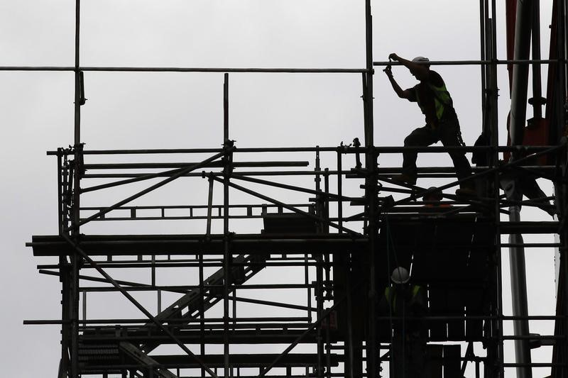 a-man-works-on-scaffolds-at-a-construction-site-photo-reuters