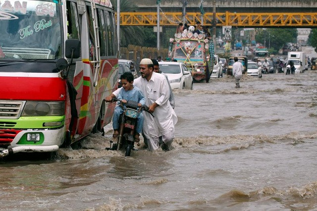 people and vehicles pass through a flooded road after the rain in karachi photo reuters