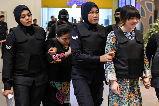 vietnamese defendant doan thi huong r and indonesian defendant siti aishah 2nd l are escorted by police personnel at the low cost carrier kuala lumpur international airport 2 klia2 in sepang during a visit to the scene of the murder as part of the shah alam high court trial process on october 24 2017 for their alleged role in the assassination of kim jong nam indonesian siti aisyah 25 and huong 28 have been charged with the murder of kim jong nam the estranged half brother of north korean leader kim jong un at kuala lumpur international airport 2 klia2 in february photo afp