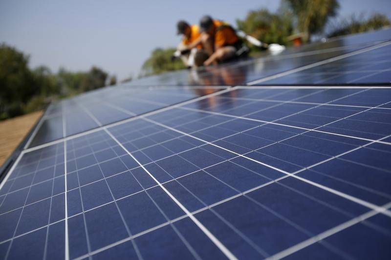 Solar technicians install solar panels on the roof of a house. PHOTO: REUTERS