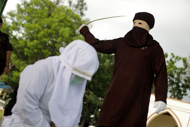 shocking images surface of indonesian woman being whipped by masked sharia enforcer
