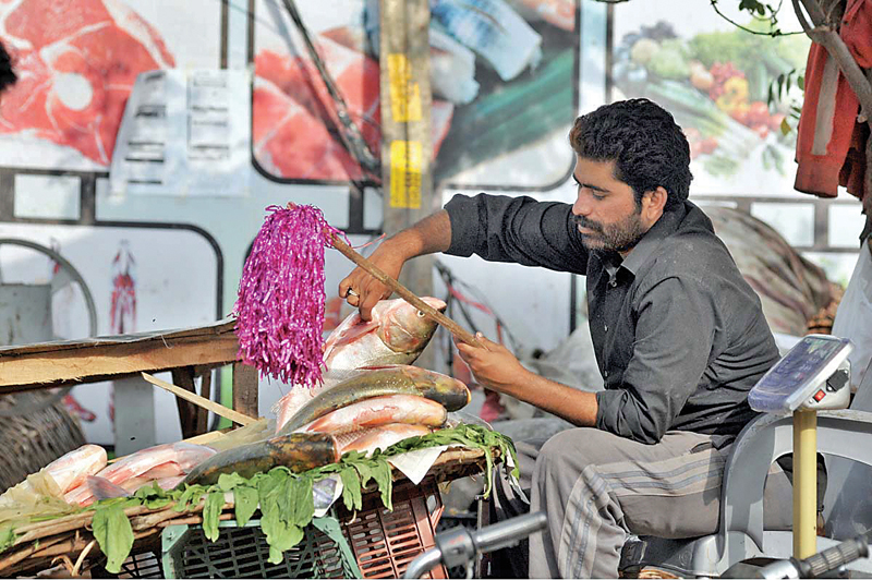 A vendor cleaning fish at his shop in the capital. Photo: APP