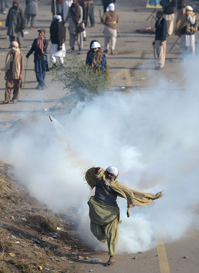 a protester of the tehreeke labaik throws a tear gas shell back towards police during a clash in islamabad on november 25 2017 photo afp