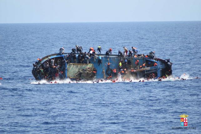 File Photo: Migrants are seen on a capsizing boat before a rescue operation by Italian navy ships 'Bettica' and 'Bergamini' off the coast of Libya in this handout picture released by the Italian Marina Militare on May 25, 2016.  PHOTO: REUTERS