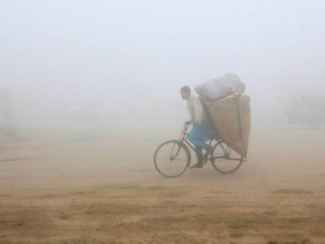 a man rides a bicycle carrying sacks of recyclables amid morning smog in lahore photo reuters