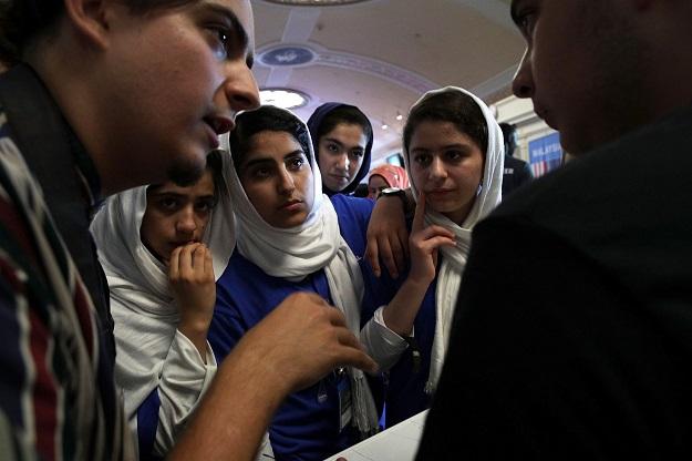 Somayeh Faruqi, Lida Azizi, Yasimin Yasinzadah, and Kawsar Roshan of Team Afghanistan listen, through embassy staff Mojib Ghaznawi's (L) translation, as they discuss strategy with a member of Team North America. PHOTO: AFP