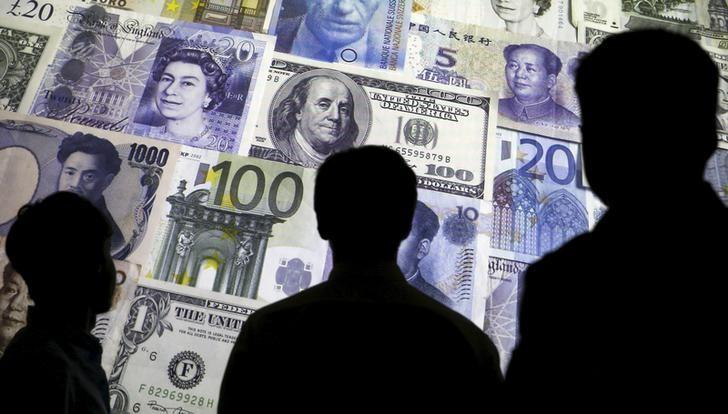 People are silhouetted against a backdrop projected with the picture of various currencies of money in this illustration taken April 4, 2016. PHOTO: REUTERS
