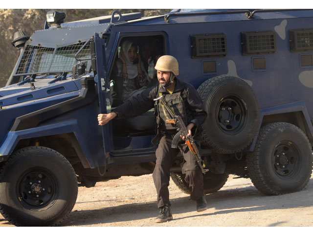 A police commando escorts rescued staff members of an Agriculture Training Institute sit in a armoured vehicle after an attack by Taliban militants in Peshawar on December 1, 2017. PHOTO: AFP