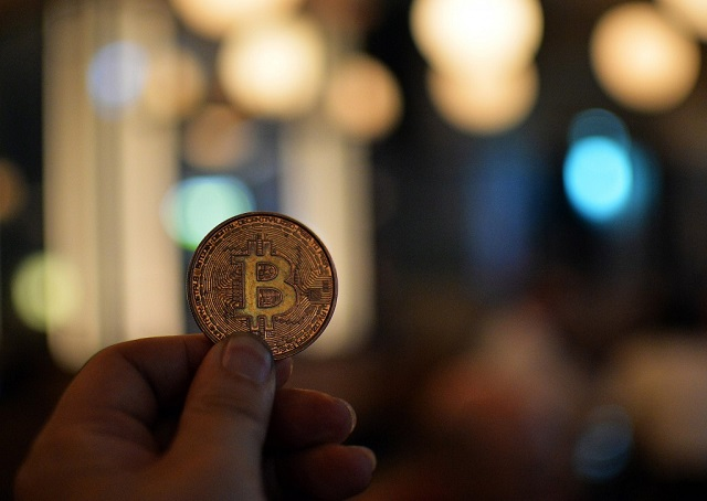 A man holds a bitcoin medal as members of bitcoin trading club hold a meeting in Tokyo. PHOTO: AFP