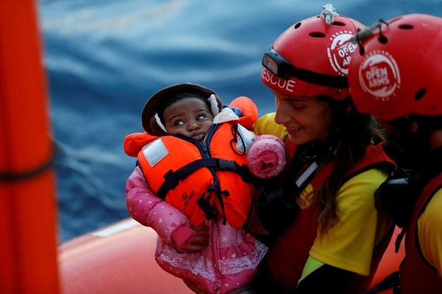 A crew member of MV Open Arms, the search and rescue ship of Proactiva Open Arms, carries a migrant baby before passing it to crew members of MV Aquarius, a search and rescue ship run in partnership between SOS Mediterranee and Medecins Sans Frontieres, during a mid-sea transfer of migrants in the central Mediterranean off the coast of Libya, December 16, 2017.     PHOTO: REUTERS