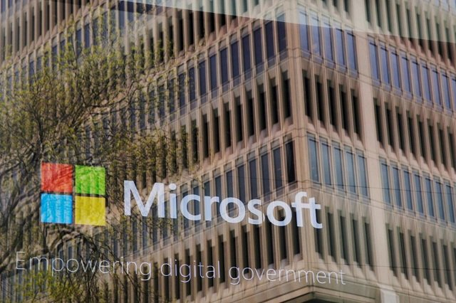 an promotional video plays behind a window reflecting a nearby building at the microsoft office in cambridge massachusetts us on may 15 2017 photo reuters