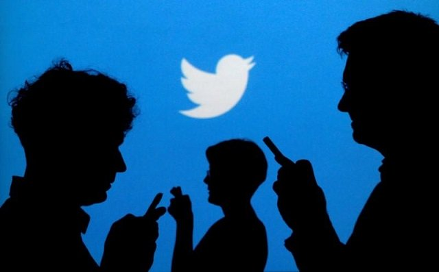 people holding mobile phones are silhouetted against a backdrop projected with the twitter logo in this illustration picture taken september 27 2013 photo reuters