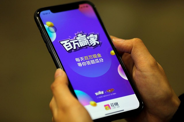 """""""Baiwan Yingjia"""", or """"Millions Winner"""", an online quiz game by live streaming app Huajiao, is seen on a mobile phone in this illustration picture taken January 22, 2018. PHOTO: REUTERS"""