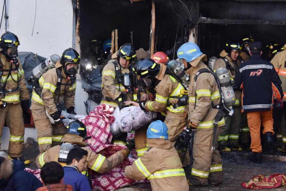 Firefighters rescue a patient from a hospital in Miryang, South Korea. Flames and toxic smoke swept through the hospital on Friday, killing at least 37 people and injuring more than 140. PHOTO: REUTERS