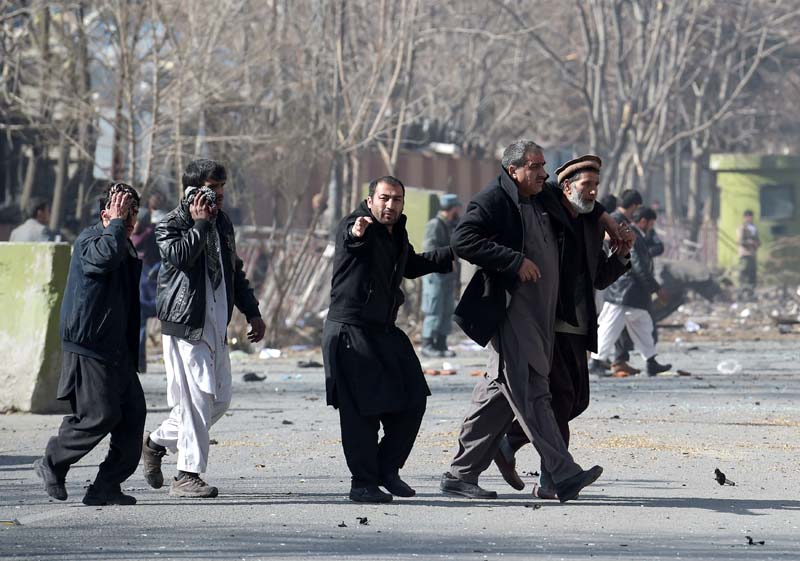 afghan volunteers help an injured men at the scene of a car bomb exploded in front of the old ministry of interior building in kabul on january 27 2018 an ambulance packed with explosives blew up in a crowded area of kabul on january 27 killing at least 17 people and wounding 110 others officials said in an attack claimed by the taliban photo afp