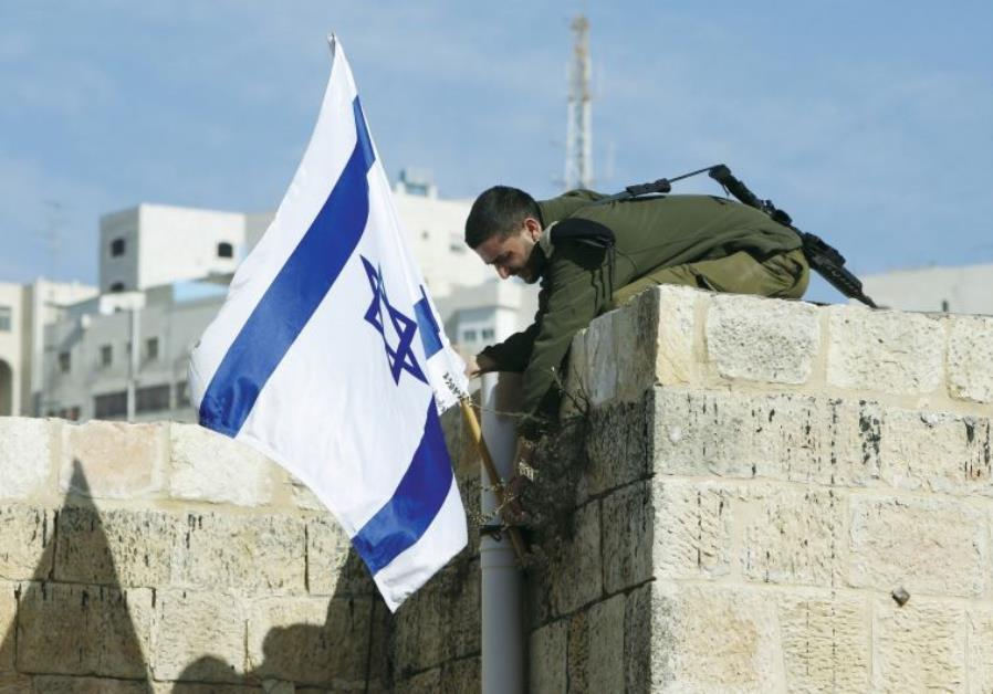 an israeli solider removes the flag from a rooftop in hebron as troops force jewish settlers out of homes they said they had purchased from palestinians photo reuters