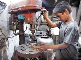 A child labourer operates a drill machine at a workshop in Lahore. PHOTO: APP