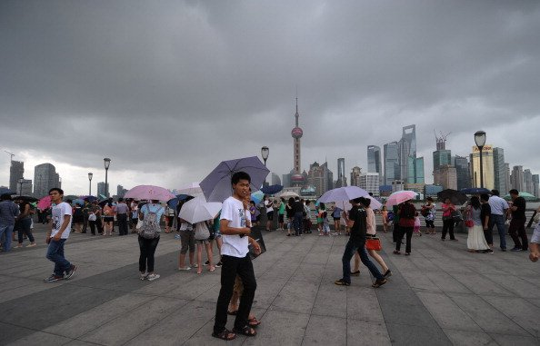 people walk along the bund as storm clouds gather over the huangpu river in shanghai on august 2 2012 photo reuters