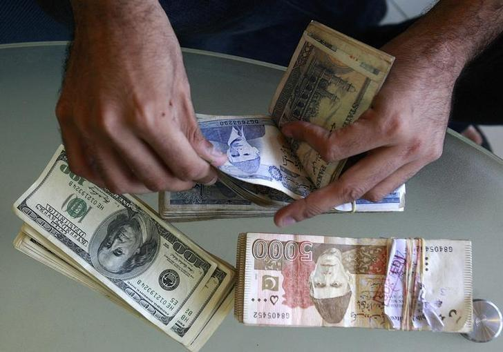 a currency dealer counts pakistani rupees and u s dollars at his shop in karachi photo reuters