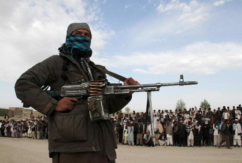 a member of the taliban insurgent and other people stand at the site during the execution of three men in ghazni province april 18 2015 photo reuters