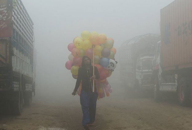 a pakistani vendor carries balloons on a street amid heavy smog in lahore photo afp