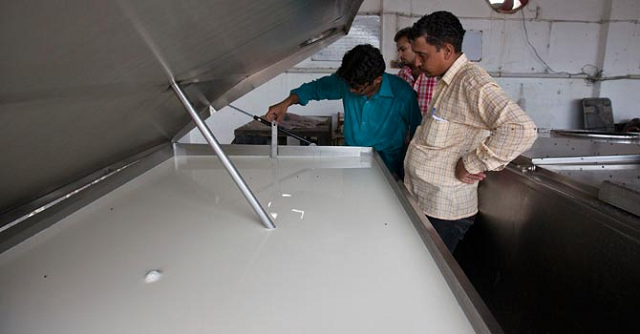 a farmer inspects the quality of milk in an industrial refrigerator at a farm in narowal photo reuters