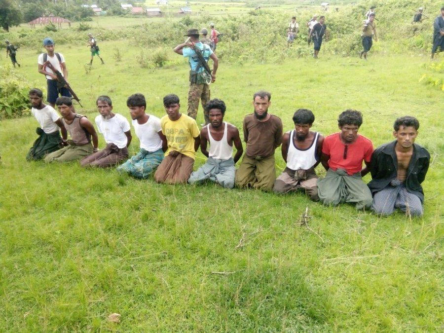 ten rohingya muslim men with their hands bound kneel as members of the myanmar security forces stand guard in inn din village photo reuters