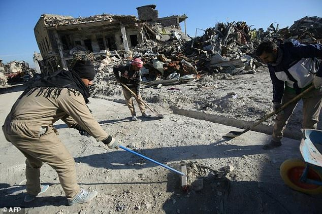 workers clean up debris from a street in mosul 039 s old city on january 8 2018 six months after iraqi forces seized the country 039 s second city from islamic state group jihadists photo afp