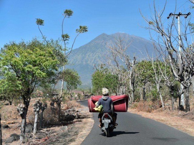 villagers return to their home in kubu village near the base of mount agung volcano in background in karangasem regency on the indonesian resort island of bali photo afp