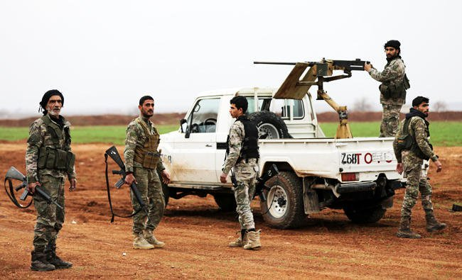 turkey backed free syrian army fighters stand around a pickup truck with a mounted weapon in the town of marea in northern aleppo countryside syria on saturday photo reuters