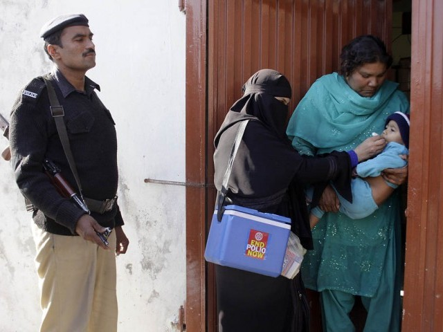 a file photo showing polio worker administering drops while a policeman stands beside her photo express file