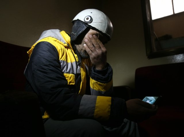 forty five year old samir salim who along with his three brothers are members of the white helmets rescue forces mourns as he looks at a picture that he took when he tried to rescue the body of his mother from under the rubble of his home in the town of medeira in syria 039 s rebel held eastern ghouta area on february 12 2018 photo afp