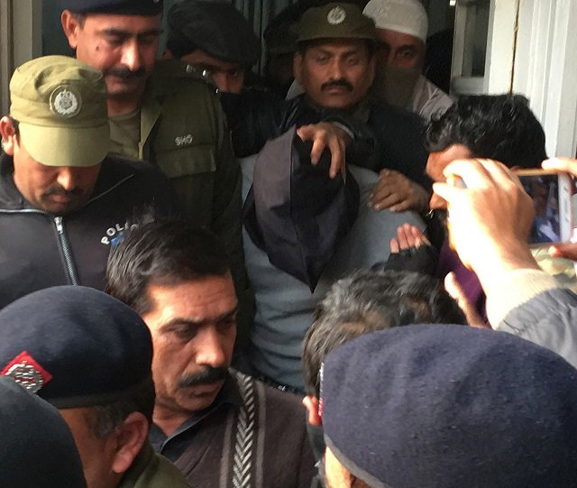 policemen escort the suspect accused of raping and murdering a young girl as they leave an anti terrorist court in lahore on january 24 2018 photo afp
