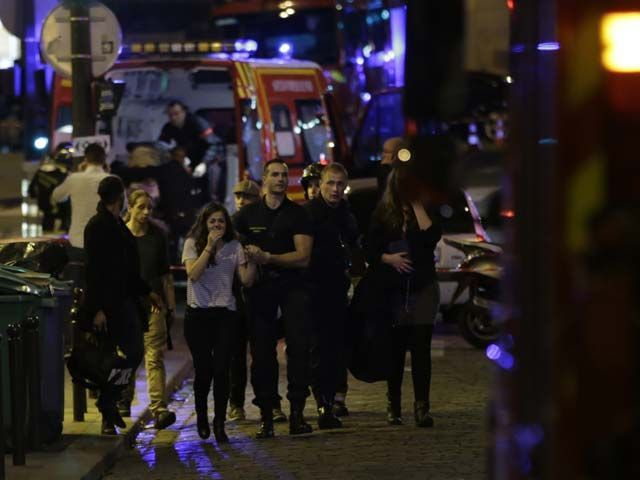 people are evacuated following an attack at the bataclan concert venue in paris on november 13 2015 at least 18 people were killed in multiple attacks in paris friday including one near the stade de france sports stadium photo afp