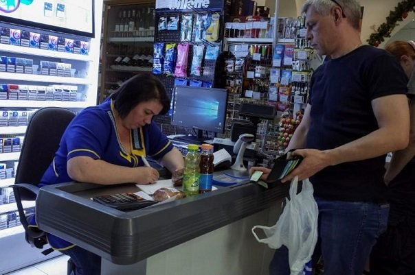a customer waits while a cashier writes out a purchase receipt for store records as many business have turned off their digital tills after cases of cyber attacks on business at a store in kiev ukraine june 28 2017 photo reuters