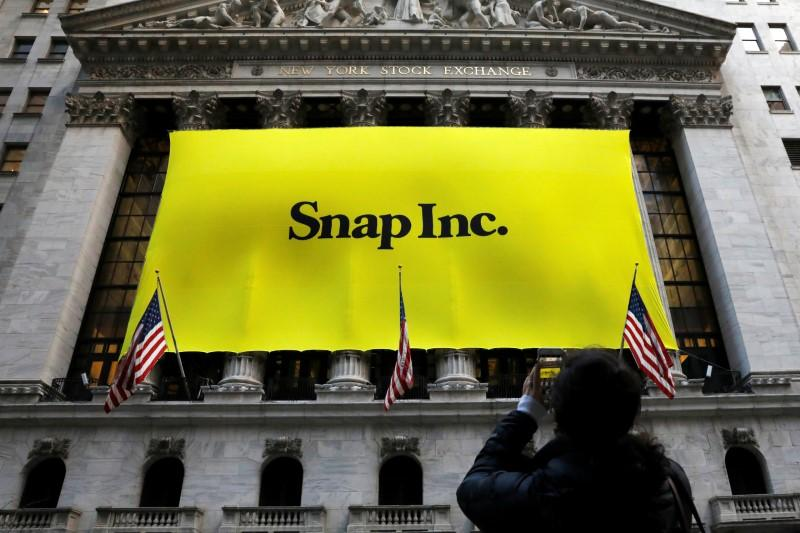 a woman photographs a banner for snap inc on the facade of the new york stock exchange nyse on the morning of the company 039 s ipo in new york city ny u s march 2 2017 photo reuters